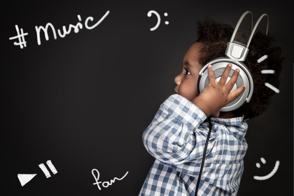 Cute little african american boy wearing earphones, listening and recording baby songs, portrait over blackboard background, happy little singer