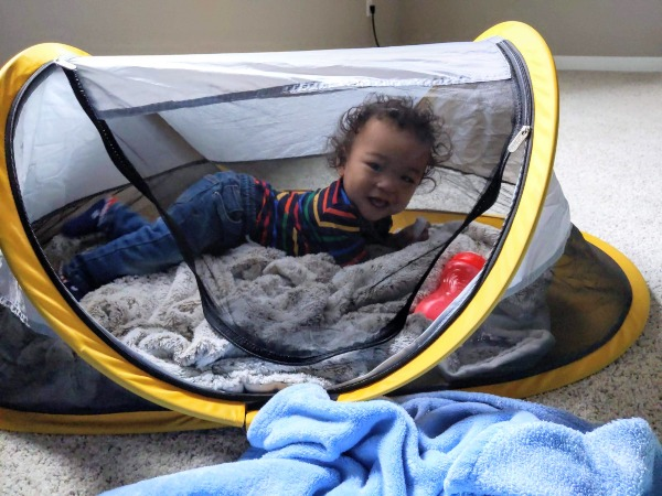 Baby smiling in Peapod travel bed