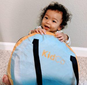 Baby holding Kidco Peapod