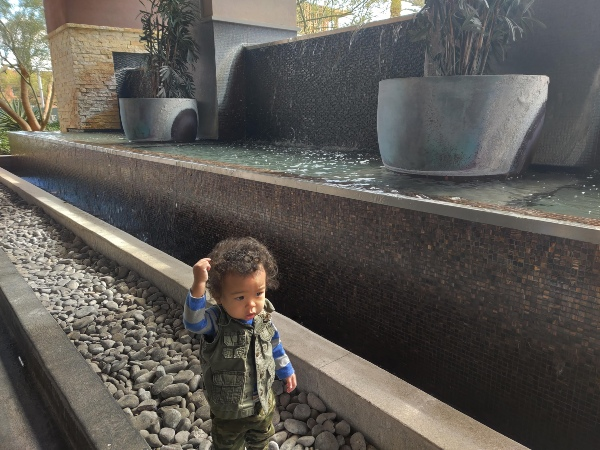 toddler playing near water fountain