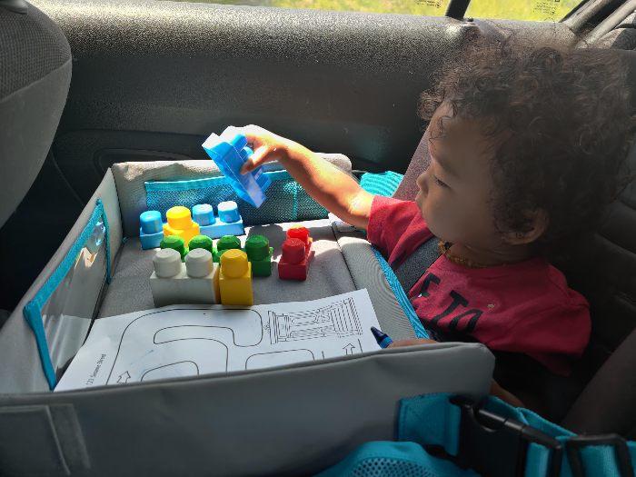 Toddler using car seat travel tray