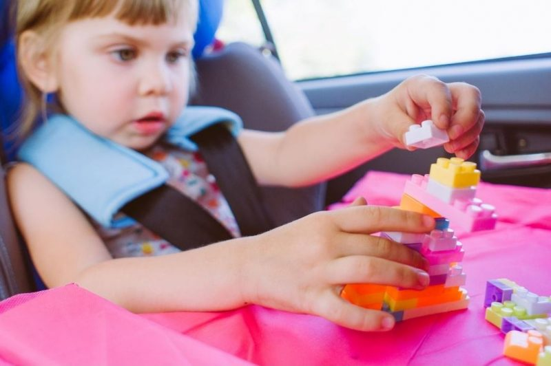 toddler on road trip playing with blocks
