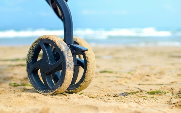 Stroller wheel in sand at the beach